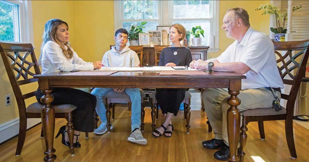 "Mary Jo Rendón and Victor Vaitkunas of Waltham High School met with junior Michael DeGloria and his mother, Johana Rodríguez, left, during a recent home visit. Vaitkunas, an electrical technology teacher, said his own positive experiences in school made him want to ""make a difference in kids' lives."""